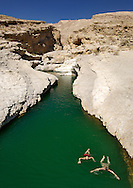Two girls swimming in the turquoise pools of Wadi Bani Khalid in the eastern Hajar mountains (Al Hajar ash sharq) of the sultanate of Oman.