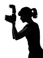 portrait silhouette in shadow of a young woman photographer holding a camera  in studio on white background isolated