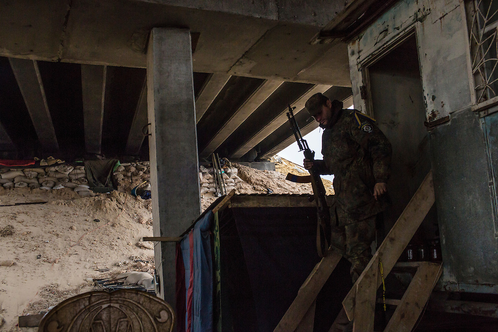 "PERVOMAISKE, UKRAINE - NOVEMBER 18, 2014: ""Skala,"" a member of the 5th platoon of the Dnipro-1 brigade, a pro-Ukraine militia, at their post underneath a bridge in Pervomaiske, Ukraine. CREDIT: Brendan Hoffman for The New York Times"