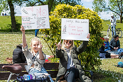 """© Licensed to London News Pictures. 16/05/2020. Manchester, UK. Two women gesture as they hold placards reading """" No mandatory vaccines """" , """" Beware Poison """" """" No 5G """" and """" Hey Bill Gates Fuck you and your vaccine """" . An anti-lockdown, """"mass gathering"""" demonstration is held in Platt Fields Park in protest at government measures to control the spread of Covid-19. A group calling itself the UK Freedom Movement has organised a series of demonstrations across the UK. Photo credit: Joel Goodman/LNP"""