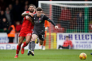 Shay McCartan of Lincoln City under pressure from Kaiyne Woolery of Swindon Town during the EFL Sky Bet League 2 match between Swindon Town and Lincoln City at the County Ground, Swindon, England on 12 January 2019.