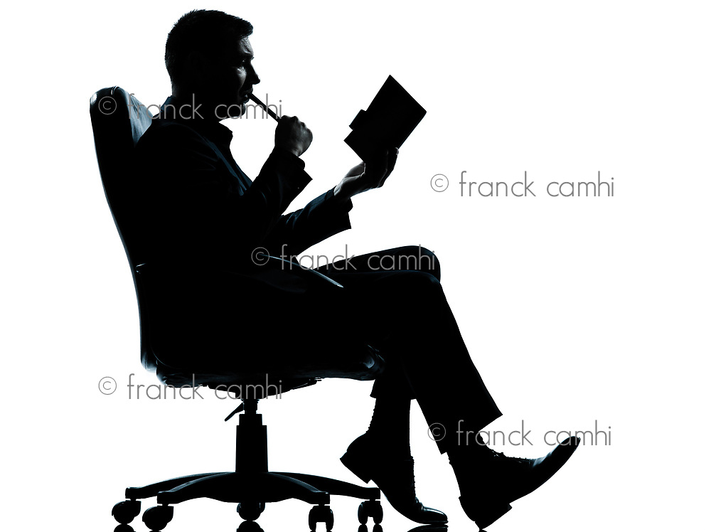 one caucasian business man sitting in armchair silhouette Full length in studio isolated on white background