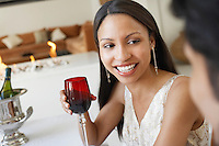 Young Woman Drinking Wine socialising at formal dinner party