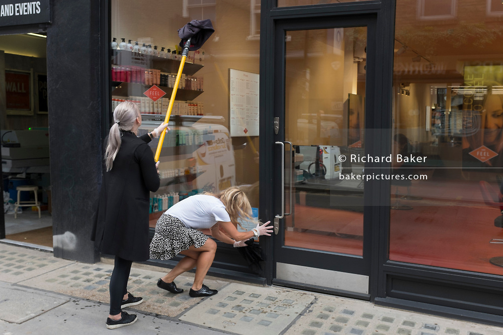 With a further 89 UK covid victims in the last 24hrs, bringing the total victims to 43,995 during the Coronavirus pandemic, pubs, restaurants and hairdressers will be able to reopen on 4th July, providing they adhere to COVID Secure guidelines. Sandra, owner of hairdressers 'Feel Soho', is helped by a friend, Brigitte, to re-open the business by cleaning the front windows, on Berwick Street in Soho, on 2nd July 2020, in London, England.