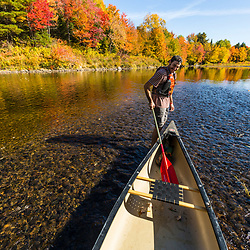 A man pulls a canoe through shallow water on the East Branch of the Penobscot River in Maine's Northern Forest. Fall.