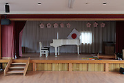 A piano on the stage of the assembly hall of an of an abandoned kindergarten inside the Fukushima exclusion zone, Namie, Fukushima, Japan. Wednesday March 9th 2016. The Great East Japan Earthquake on March 11th 2011 was followed by a massive tsunami that levelled much of the Tohoku coast in north east Japan, killing around 18,000 people and causing meltdowns and explosions at the Fukushima Daiichi nuclear power station leading to the contamination and evacuation of a 20 kilometre exclusion zone around the plant.