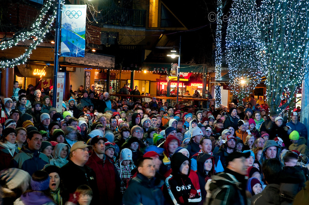 People fill Village Square in Whistler, BC for the 2010 Winter Olympic Games opening ceremony broadcast from Vancouver.