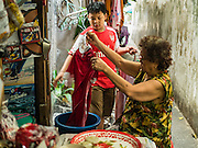 07 APRIL 2016 - BANGKOK, THAILAND: A boy helps his grandmother with their laundry next to their home in the squatters' community in Mahakan Fort. Mahakan Fort was built in 1783 during the reign of Siamese King Rama I. It was one of 14 fortresses designed to protect Bangkok from foreign invaders, and only of two remaining, the others have been torn down. A community developed in the fort when people started building houses and moving into it during the reign of King Rama V (1868-1910). The land was expropriated by Bangkok city government in 1992, but the people living in the fort refused to move. In 2004 courts ruled against the residents and said the city could take the land. The final eviction notices were posted last week and the residents given until April 30 to move out. After that their homes, some of which are nearly 200 years old, will be destroyed.       PHOTO BY JACK KURTZ