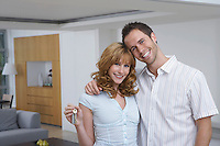 Couple embracing woman holding key in new home portrait