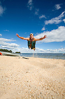 Young man jumping on beach for a frisbee. Lake Sebago, Maine