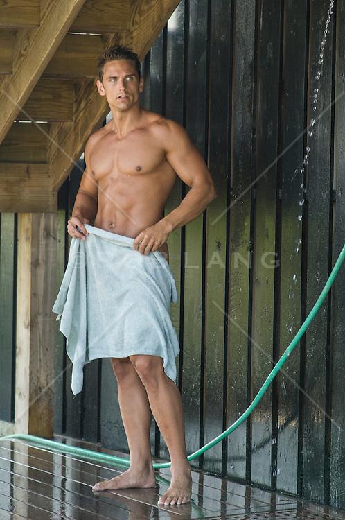 bodybuilder toweling off in an outdoor shower