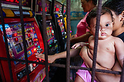 """08 JANUARY 2007 - MANAGUA, NICARAGUA:  A woman holds her baby while she plays the slot machines in a """"casino"""" in Mercado Oriental, the main market that serves Managua, Nicaragua. The market encompasses dozens of square blocks and is the largest market in Central America. The government of Violetta Chamorro legalized gambling in 1990. There are casinos in most of the tourist hotels and dozens of small """"mom and pop"""" slot machine casinos in the market. Photo by Jack Kurtz"""