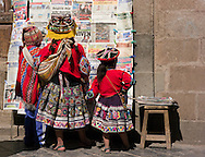 Children in typical dress reading the day's newspapers, Cusco, Peru