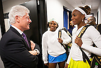 Former President Bill Clinton chats with tennis stars Serena and Venus Williams.