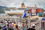 """Passengers wait to depart and embark at the seaport in Jayapura, the capital of Papua, which is the main entry point for goods and migrants entering and exiting the region.<br /> <br /> Papua is a vast province and has abundant natural resources such as copper, gold, and timber.  However, most indigenous Papuans live on less than $1 a day.  The incidence of poverty in Papua is the highest in the country; double that of the national average.  Papua was acquired by Indonesia in 1969 in a disputed vote rejected by most Papuans.  For the past four decades Papuans have sought independence.  A transmigration policy implemented by the federal government relocated almost a million non-Papuan migrants from surrounding provinces as part of the """"Indonesianization"""" process.  These migrants, along with another million voluntary migrants, dominate most of the region's trade and business, thereby controlling authority and dictating commerce in Papua.  Imported goods such as rice, medication, and gas are brought into Papua and sold at exorbitant prices, making the cost of living the highest in Indonesia.  Coupled with unequal access to education and training, opportunities for indigenous Papuans to advance economically are limited.  The consequence is economic inequality¬--wealthy migrants and poor Papuans--and a marginalized indigenous population where poverty, unemployment, malnourishment, illness, illiteracy, and discrimination are the norm."""