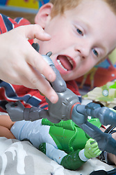 Little boy playing with action figures in his bedroom,