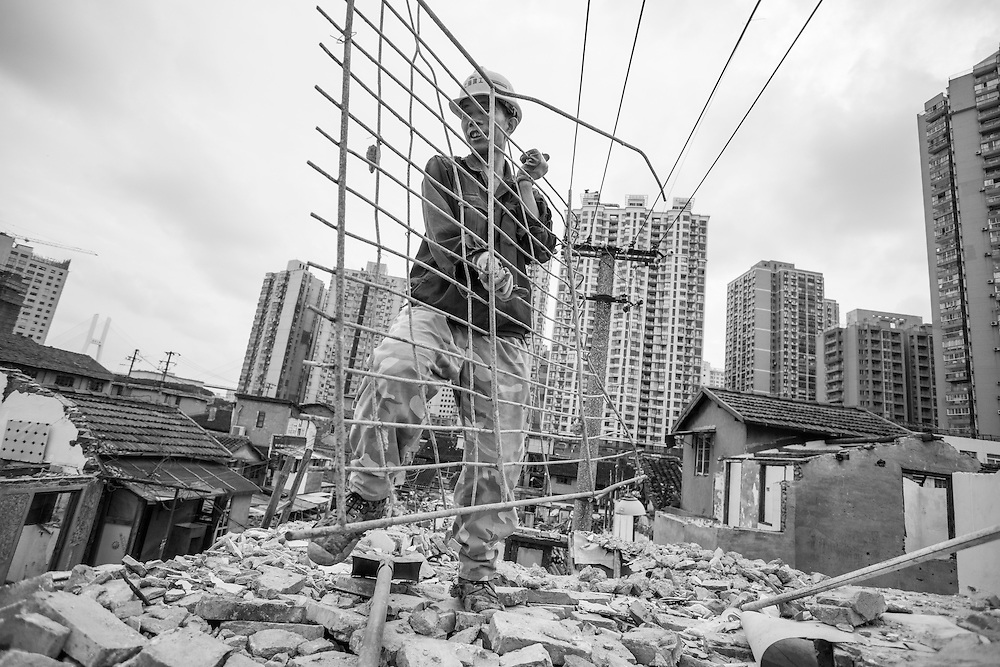 China, Shanghai, Workman carries steel reinforcement from roof of building demolition site