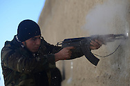 Aleppo, Syria, December, 2012 -  A Free Syrian Army rebel shoots at a Syrian Army position and gets sprayed by fragments of the wall during an operation to close the rebels' grip around the airport area, which is still under government control. (Photo by Miguel Juárez Lugo)