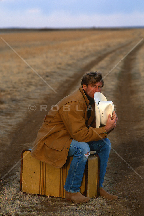 Man sitting on a suitcase  in the middle of a dirt road in New Mexico