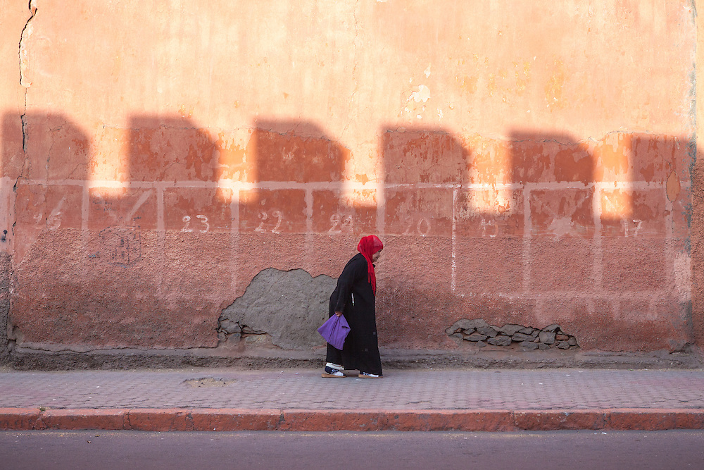Arab muslim woman wearing a red headscarf on the streets of Marrakech, Morocco, at sunset. Shot in the old mellah (Jewish quarter).