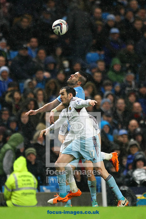 Picture by Paul Chesterton/Focus Images Ltd +44 7904 640267<br /> 08/01/2014<br /> Alvaro Negredo of Man City and Joey O'Brien of West Ham in action during the Capital One Cup Semi Final 1st Leg match at the Etihad Stadium, Manchester.