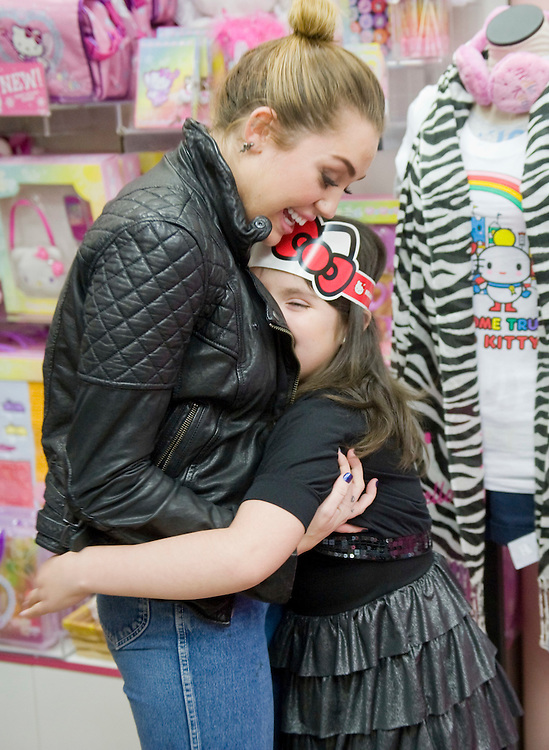 """Miley Cyrus gets a big hug from Jadzia Acosta, 8, who came with her mother from Miami to meet Cyrus at the Sanrio Store in South Coast Plaza as part of a Make A Wish Foundation's wish-granting. Jadzia had earlier squealed with delight upon meeting the life-sized Hello Kitty mascot in the store, but Miley? """"I felt happy,"""" she said, and then, after thinking about it a little more, added: """"A lot, a lot, a lot!"""""""