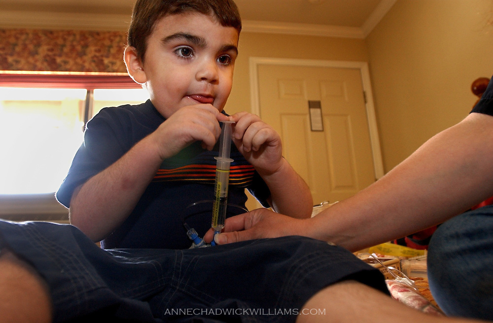 Tommy Bennett, 3, pushes a syringe of medicine into the central lines attached in his body to help him combat his disease. Bennett and his two older siblings have Sanfilippo syndrome, a rare genetic disease. The family will be heading back to North Carolina soon for a third attempt at a procedure to help Tommy. June 19, 2003..