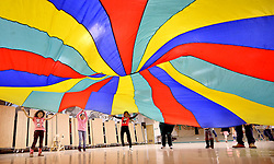 Henderson Elementary student May Reilly Rubio, center, holds on to a giant rainbow parachute as she and her classmates shake it up and down throwing a ball into the air Wednesday as part of a game night celebrating students perfect attendance for the semester at the school.