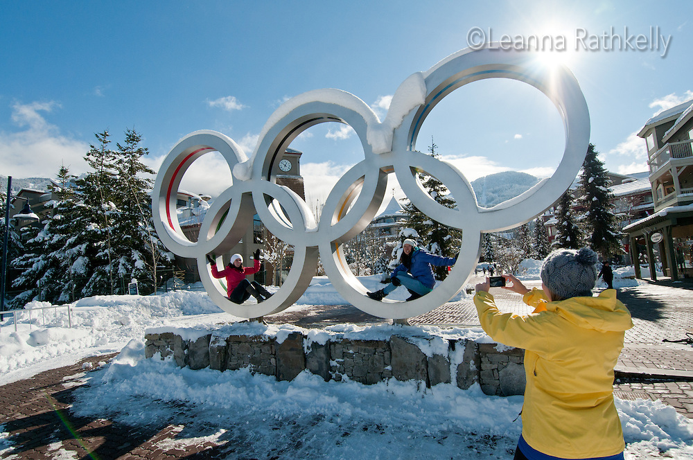 A trio of women take photos at the Olympic Rings in Whistler Village on a winter day.