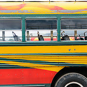 Side detail of a chicken buses behind the Mercado Municipal (town market) in Antigua, Guatemala. From this extensive central bus interchange the routes radiate out across Guatemala. Often brightly painted, the chicken buses are retrofitted American school buses and provide a cheap mode of transport throughout the country.