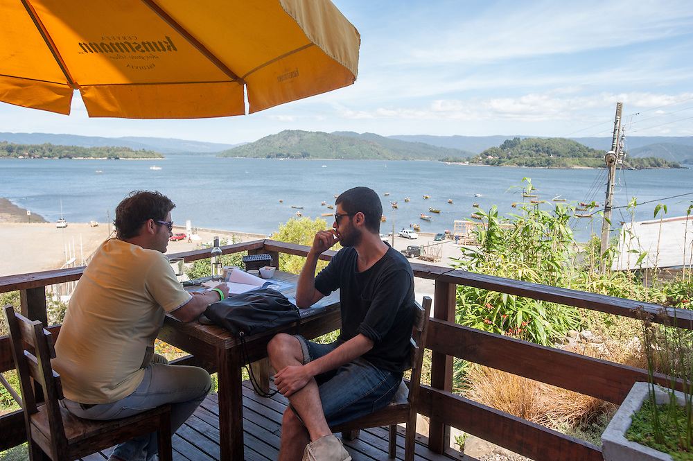 Two men at a Restaurant Table overlooking the lagoon, Pueto Varas, Chile