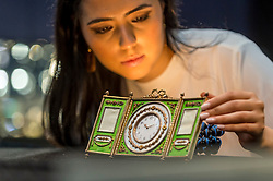 "© Licensed to London News Pictures. 31/05/2019. LONDON, UK. A staff member views ""A rare Fabergé silver-gilt enamel and seed pearl triptych clock and frame"" by workmaster Johan Victor Aarne, 1880-1904 (Est. GBP 150,000-200,000) at a preview of works from the upcoming sale of Russian Pictures, Works of Art, Fabergé & Icons Sales at Sotheby's, New Bond Street, on 4 June 2019.  Photo credit: Stephen Chung/LNP"
