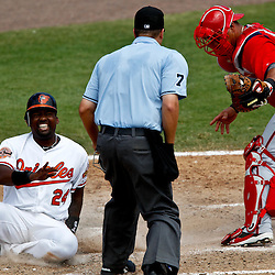 March 24, 2012; Sarasota, FL, USA;  Baltimore Orioles designated hitter Wilson Betemit (24) reacts after being tagged out at home plate by Washington Nationals catcher Wilson Ramos (3) during the bottom of the fourth inning of a spring training game at Ed Smith Stadium.  Mandatory Credit: Derick E. Hingle-US PRESSWIRE