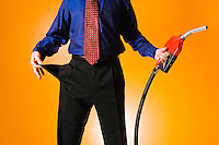 The mid section of a man in a shirt and tie holding a gasoline nozzle and pulling his pocket inside-out to illustrate the idea of having no money to buy fuel.