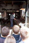 Children watch blacksmith -shallow depth of field on central boy's head- Zuiderzee museum, Enkhuizen, Netherlands