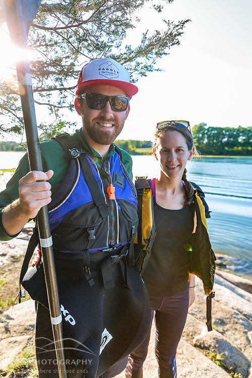 A couple takes a break from kayaking on the Essex River at the Cox Reservation in Essex, Massachusetts.