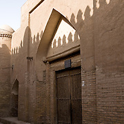 Shadow of city wall on the caravanserai doors, Khiva