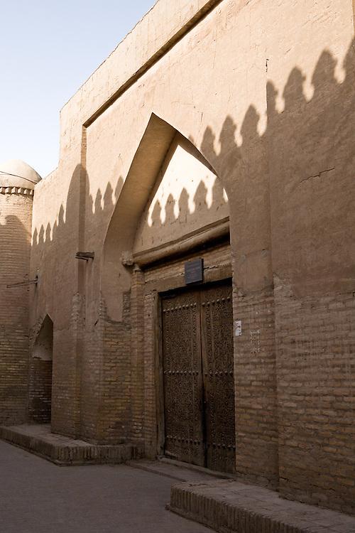 Shadow of city wall on the caravanserai doors, Khiva
