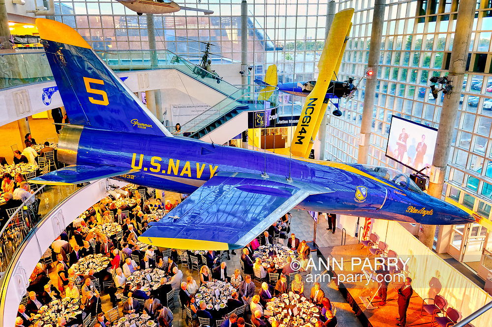 Garden City, New York, U.S. June 6, 2019. On stage are (at lectern) MICHAEL STROMER, JetBlue Chief Product Officer, Techology; and MARC MACDONNELL, Chair, Board of Directors of Cradle of Aviation, as seen from third level of atrium of CAM, during Apollo at 50 Anniversary Dinner, an Apollo astronaut tribute celebrating the Apollo 11 mission Moon landing. U.S. Navy Blue Angels Grumman F-11A Tiger jet is suspended from ceiling. Astronauts and Nassau County Executive Laura Curran are seated at tables next to stage.