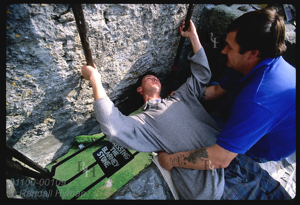 'Holder' Nigel Barrows helps man lean back to kiss Blarney Stone atop 130' Blarney Castle. Ireland