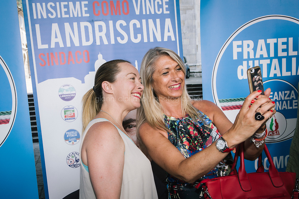 COMO, ITALY - 21 JUNE 2017: Giorgia Meloni (left), leader of the Fratelli d&rsquo;Italia party, takes a selfie with a supporter at the end of Mr Landriscina's rally in Como, Italy, on June 21st 2017.<br /> <br /> Residents of Como are worried that funds redirected to migrants deprived the town&rsquo;s handicapped of services and complained that any protest prompted accusations of racism.<br /> <br /> Throughout Italy, run-off mayoral elections on Sunday will be considered bellwethers for upcoming national elections and immigration has again emerged as a burning issue.<br /> <br /> Italy has registered more than 70,000 migrants this year, 27 percent more than it did by this time in 2016, when a record 181,000 migrants arrived. Waves of migrants continue to make the perilous, and often fatal, crossing to southern Italy from Africa, South Asia and the Middle East, seeing Italy as the gateway to Europe.<br /> <br /> While migrants spoke of their appreciation of Italy&rsquo;s humanitarian efforts to save them from the Mediterranean Sea, they also expressed exhaustion with the country&rsquo;s intricate web of permits and papers and European rules that required them to stay in the country that first documented them.