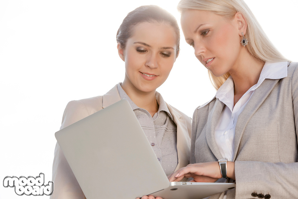 Young businesswomen using laptop against clear sky