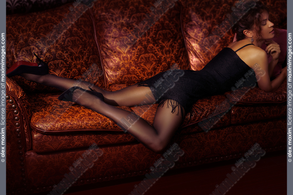 Sensual portrait of a beautiful sexy woman lying on a luxurious couch wearing a short black dress, black stockings and high heel shoes