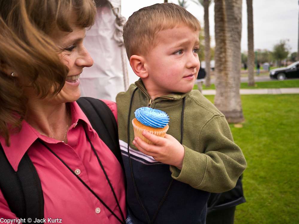 14 FEBRUARY 2012 - PHOENIX, AZ:   A boy carries a birthday cupcake for the state centennial at the State Capitol in Phoenix, Feb 14. Arizona's statehood day is February 14 and this year Arizona marked 100 years of statehood. It was the last state in the 48 contiguous United States.  PHOTO BY JACK KURTZ
