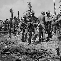 U.S. Marines advancing to the front lines on Namur Island walk past the body of a fallen Japanese soldier. Burial will come later when the troops have had a chance to rest adn get everything shipshape.