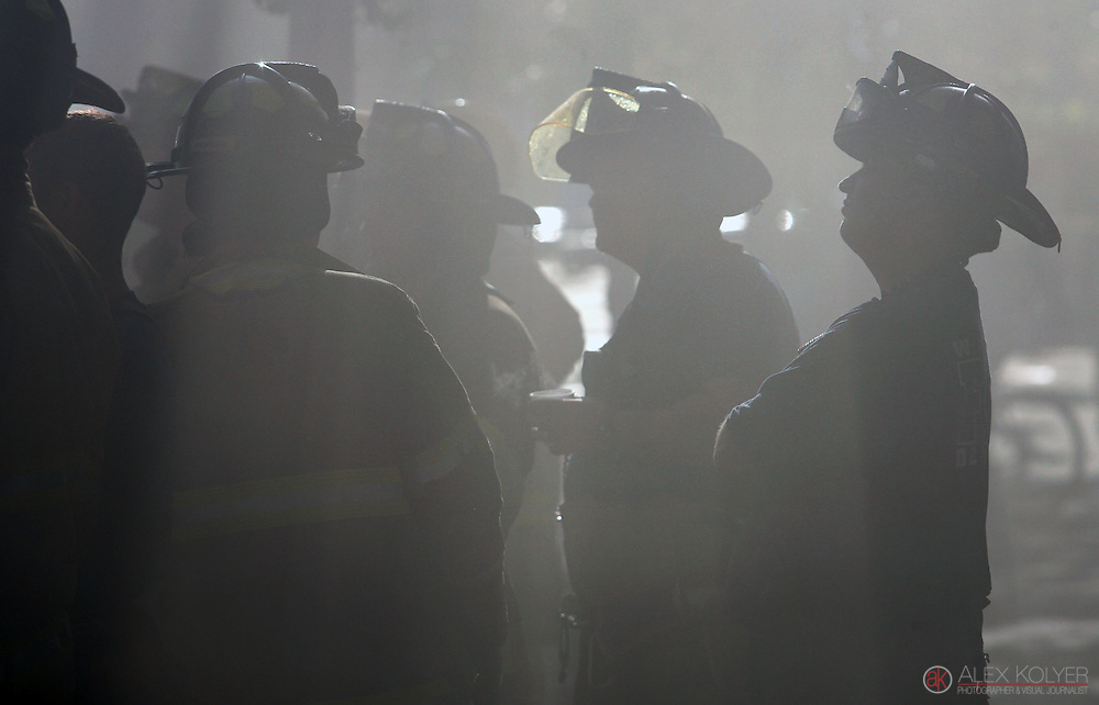 9/13/13--Winona<br /> Firefighters gather on the sidewalk as others fight to extinguish a fire that destroyed three buildings in downtown Winona, Minn., Friday morning, Sept. 13, 2013. (Photo for MPR News by Alex Kolyer)