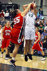 10 January 2009: Lisa Gartelos blocks the shot being offered by Christina Solara. The Illinois Wesleyan Titans, ranked #1 in the latest USA Today/ESPN poll, take down the Lady Reds of Carthage and remain undefeated,  2-0 in the CCIW and over all to 12-0. This is the first time in the history of the Lady Titans Basketball they have been ranked #1 The Titans and Lady Reds played in the Shirk Center on the Illinois Wesleyan Campus in Bloomington Illinois.