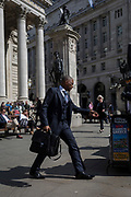A stylish businessman wearing a 3-piece suit strides below the classical architecture of Royal Exchange and the WW1 war memorial at Bank Triangle, on 10th May 2017, in the City of London, England.