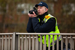 Luton, UK. 5th May, 2012. A police officer gathers intelligence on supporters of Unite Against Fascism attending the We Are Luton/Stop The EDL march, held in protest against a march by the far-right English Defence League.