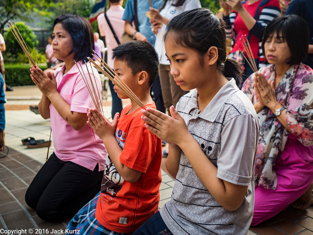 13 OCTOBER 2016 - BANGKOK, THAILAND: A family prays for Bhumibol Adulyadej, the King of Thailand, at Siriraj Hospital Thursday morning before the King's death was announced. Thousands of people came to the hospital to pray for the beloved monarch. Bhumibol Adulyadej, the King of Thailand, died at Siriraj Hospital in Bangkok Wednesday, October 13, 2016. Bhumibol Adulyadej, 5 December 1927 – 13 October 2016, was the ninth monarch of Thailand from the Chakri Dynasty and is known as Rama IX. He became King on June 9, 1946 and served as King of Thailand for 70 years, 126 days. He was, at the time of his death, the world's longest-serving head of state and the longest-reigning monarch in Thai history.       PHOTO BY JACK KURTZ